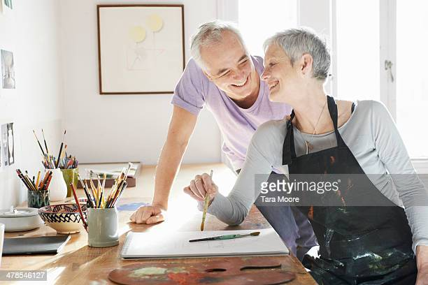 mature man and woman in artists's studio - mature couple stock pictures, royalty-free photos & images