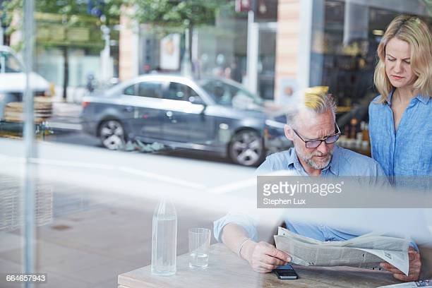 Mature man and woman in cafe, reading newspaper, street reflected in window