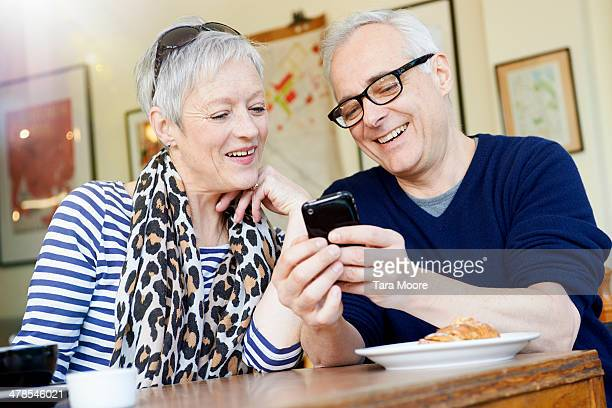 mature man and woman in cafe with mobile