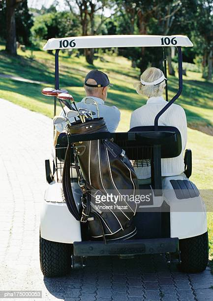 Mature man and woman in golf cart, rear view