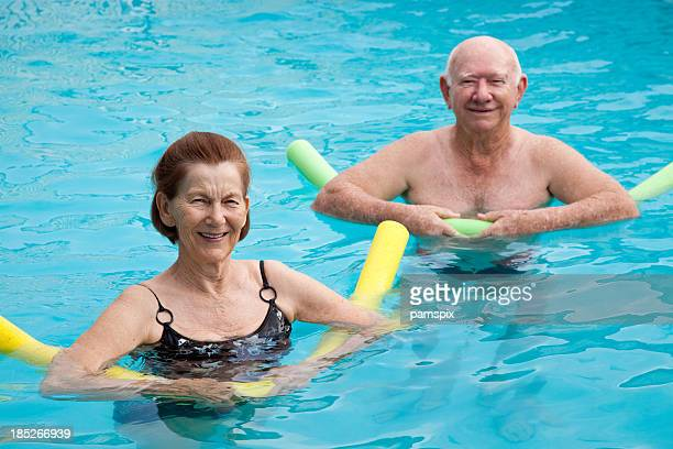 Mature man and woman in pool with pool noodles