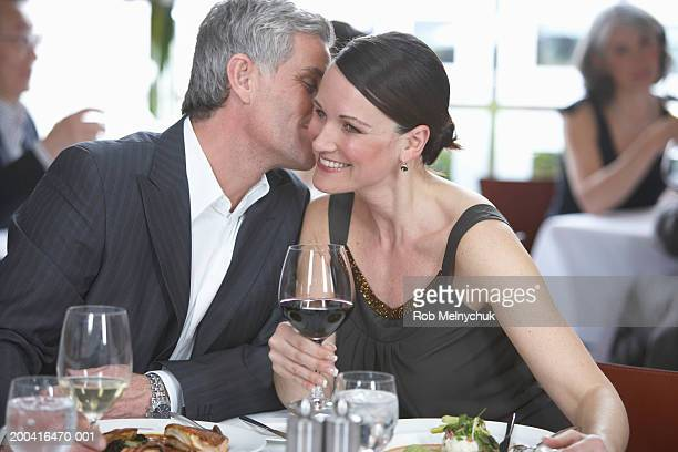 Mature man and woman in restaurant, man whispering in woman's ear