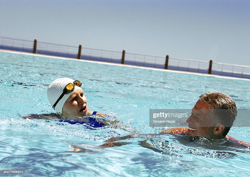 Mature man and woman in swimming pool : Stock Photo