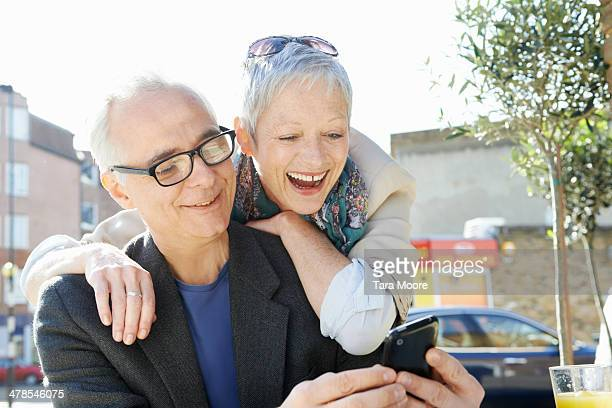 mature man and woman laughing looking at mobile