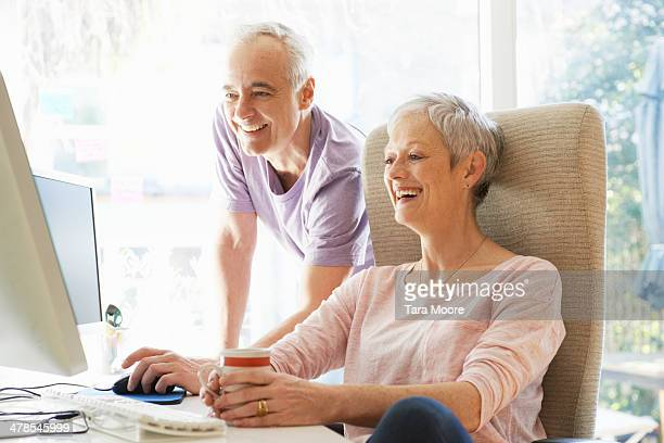 mature man and woman laughing using computer - 50 59 years stock pictures, royalty-free photos & images