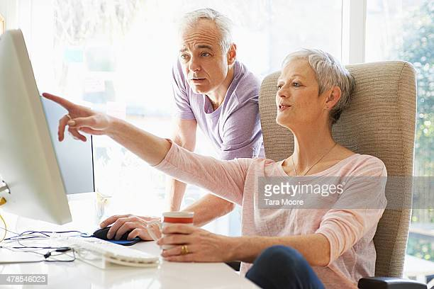 mature man and woman looking at home computer - 50 59 years stock pictures, royalty-free photos & images