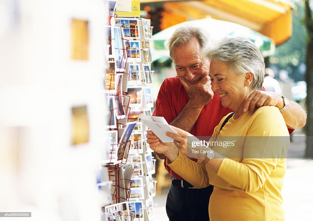 Mature man and woman looking at postcards in the street : Stockfoto