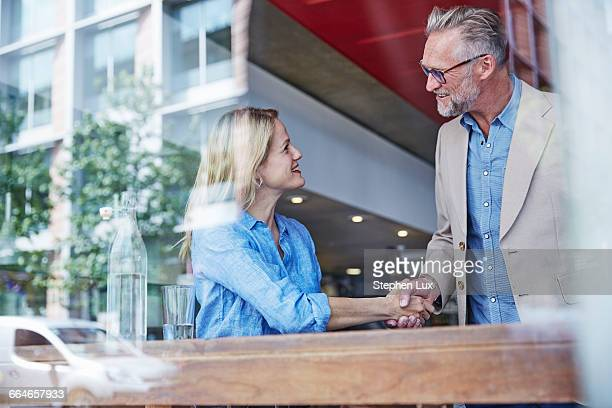 Mature man and woman meeting in cafe, shaking hands