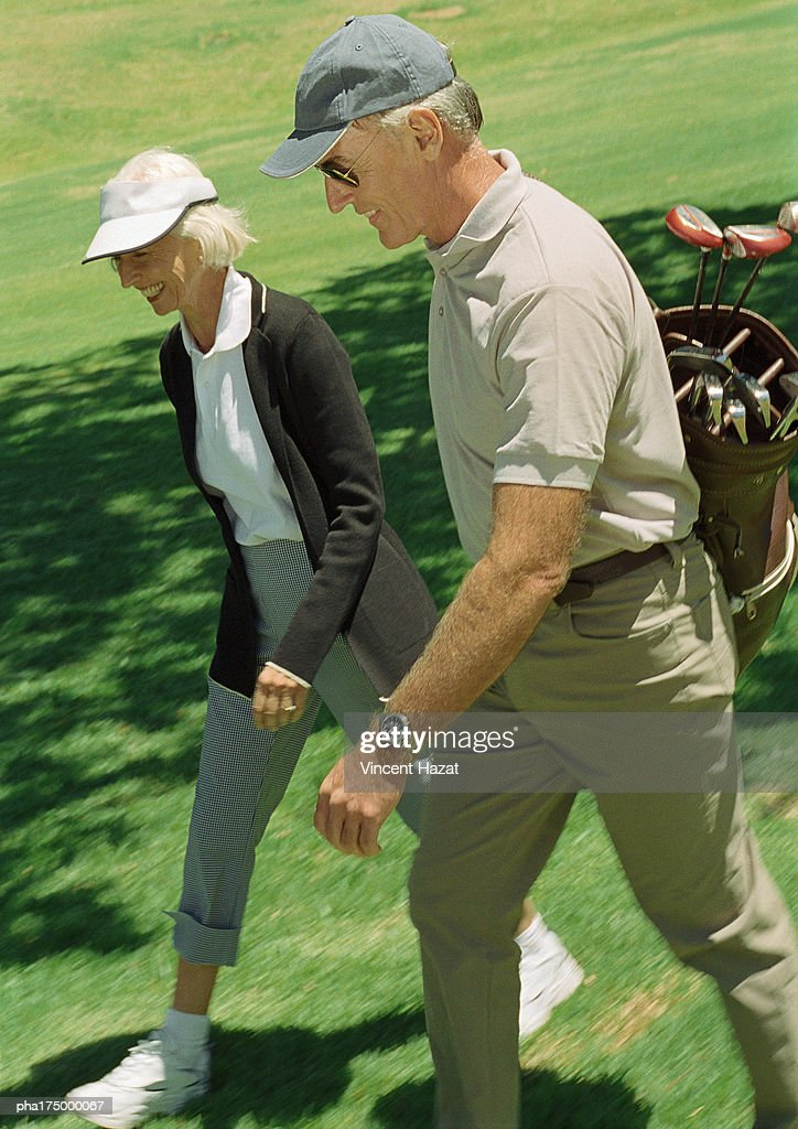 Mature man and woman on green, man carrying golf clubs : Stockfoto