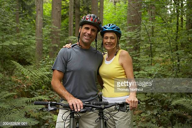 Mature man and woman on mountain bikes in forest, smiling, portrait