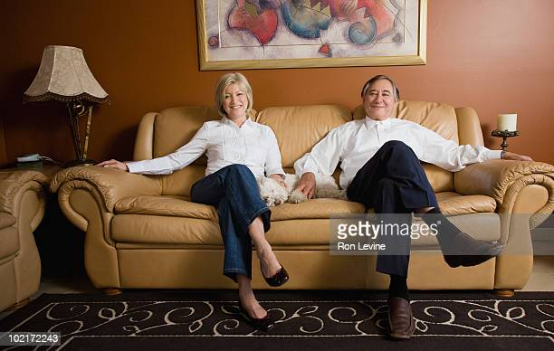 mature man and woman on sofa with pet dog - one animal stock pictures, royalty-free photos & images