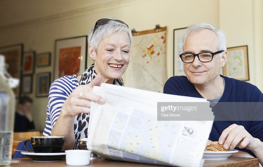 mature man and woman reading newspaper in cafe : Stock Photo