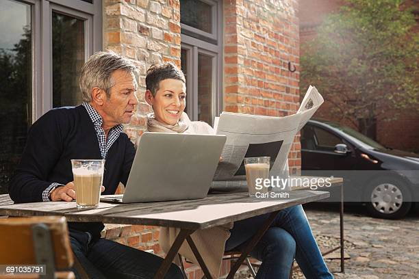 Mature man and woman reading newspaper while sitting with laptop in back yard