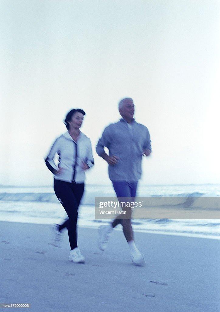 Mature man and woman running on beach : Stockfoto