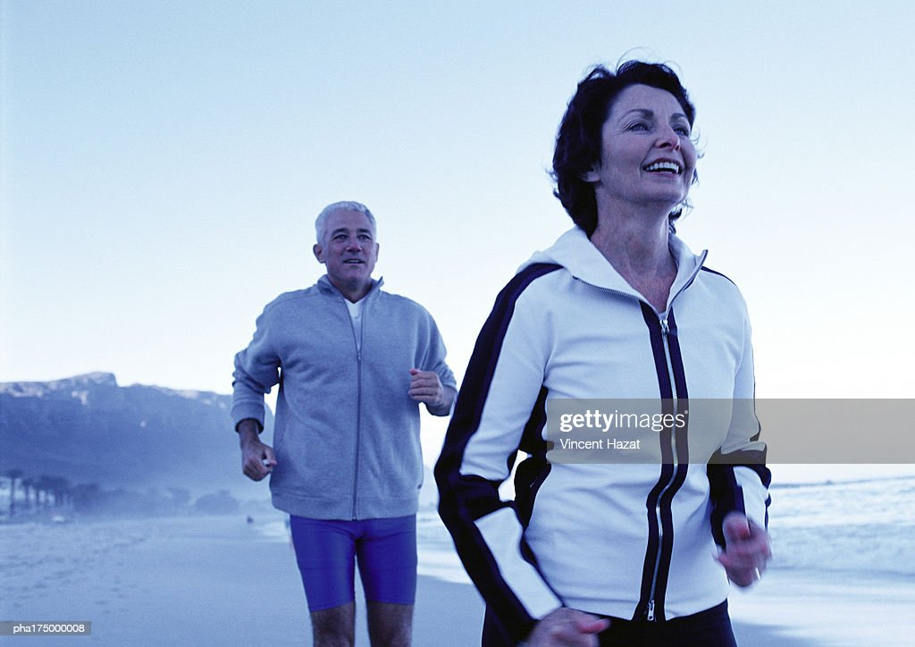 Mature man and woman running on beach, side view : Stockfoto