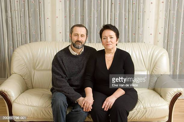 Mature man and woman sitting on sofa, holding hands, portrait