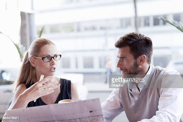 Mature man and woman, sitting outside cafe, having discussion