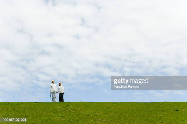 Mature man and woman standing atop hillside, low angle view