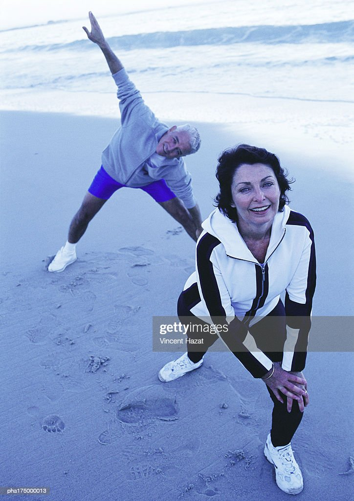 Mature man and woman warming up on beach : Stockfoto