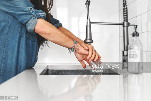 mature man and woman washing hands - kitchen sink stock pictures, royalty-free photos & images