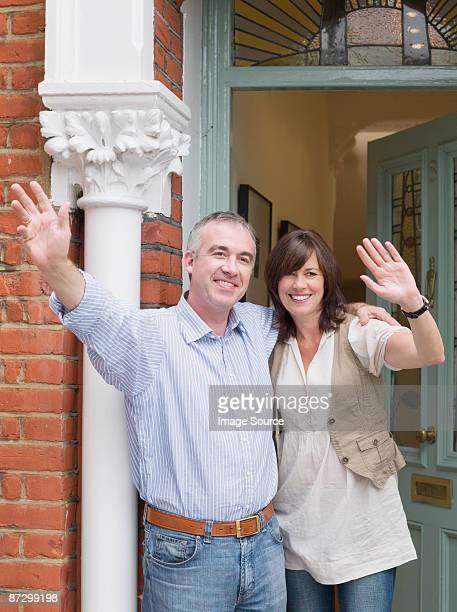 Mature man and woman waving