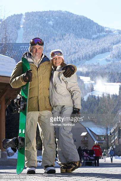 Mature man and woman with snowboard, smiling, portrait
