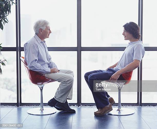 Mature man and young man sitting in chairs opposite each other