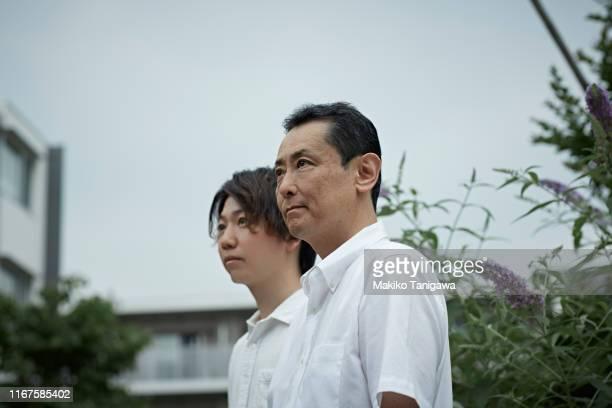 mature man and young man wearing white shirt - makiko tanigawa ストックフォトと画像