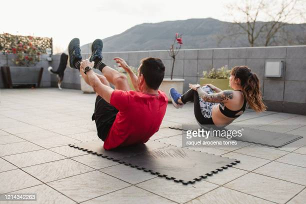 mature man and young woman doing crunches with sportswear on the terrace of his house at sunset - on the move imagens e fotografias de stock
