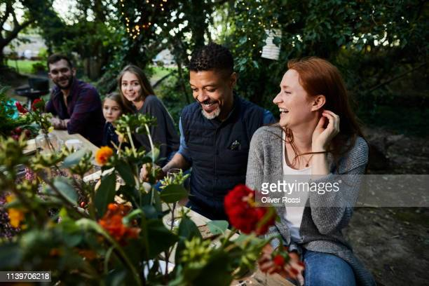 mature man and young woman laughing on a garden party - kleine personengruppe stock-fotos und bilder