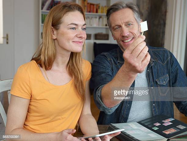 Mature man and young woman looking through stamp collection