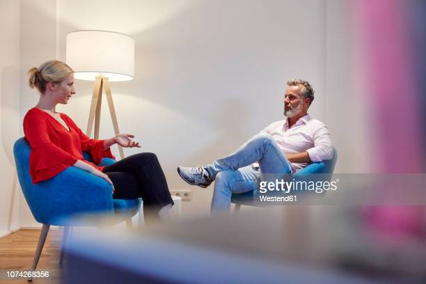 mature man and young woman sitting in armchairs talking - focus on background stock pictures, royalty-free photos & images