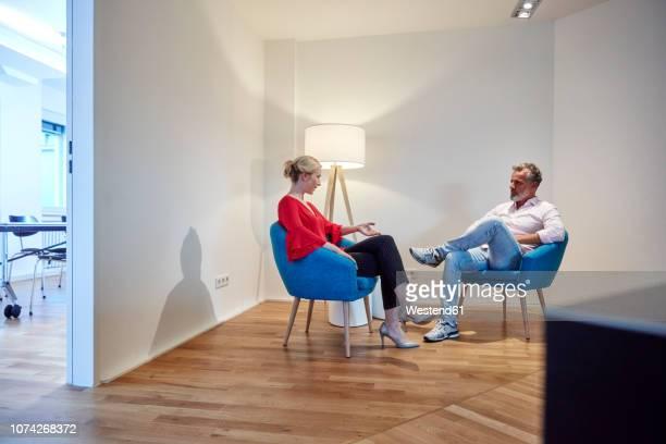 mature man and young woman sitting in armchairs talking - armstoel stockfoto's en -beelden