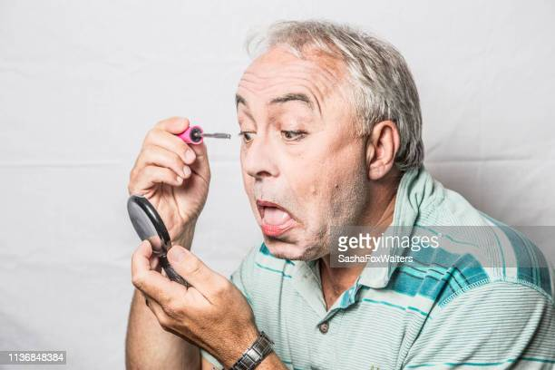 mature man applying make-up - mascara stock pictures, royalty-free photos & images