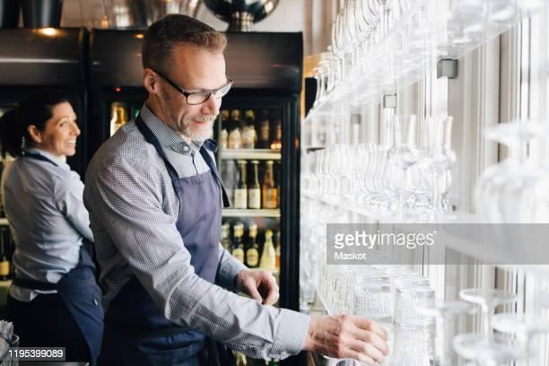 mature man arranging wineglasses while waitress in background at restaurant - voedingsindustrie stockfoto's en -beelden