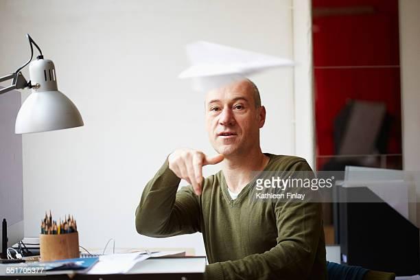 Mature man at desk throwing paper airplane