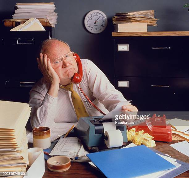 mature man at desk with adding machine and telephone - headhunters stock pictures, royalty-free photos & images