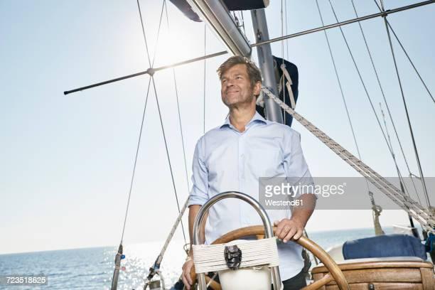 Mature man at helm of his sailing boat