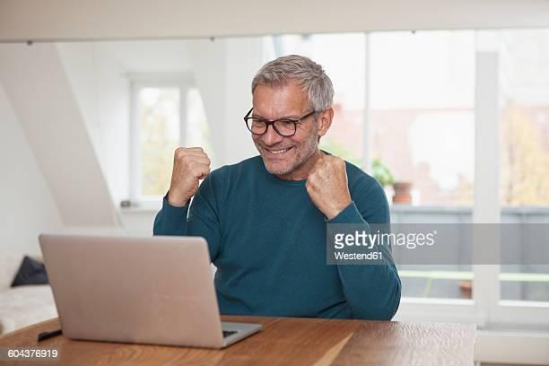 Mature man at home looking at laptop cheering