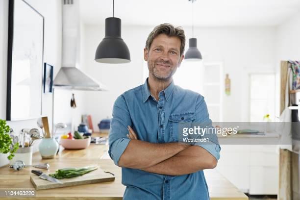 mature man at home, looking confidet - blick in die kamera stock-fotos und bilder