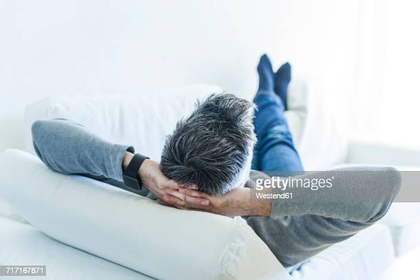 Mature man at home lying on couch