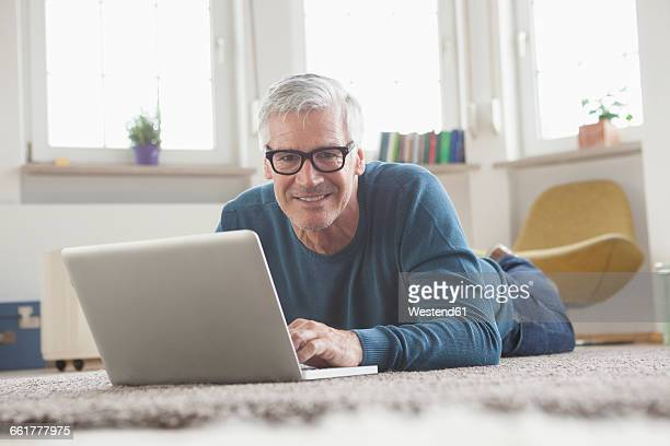 mature man at home lying on floor using laptop - one man only stock pictures, royalty-free photos & images