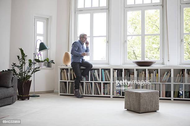 Mature man at home on the phone