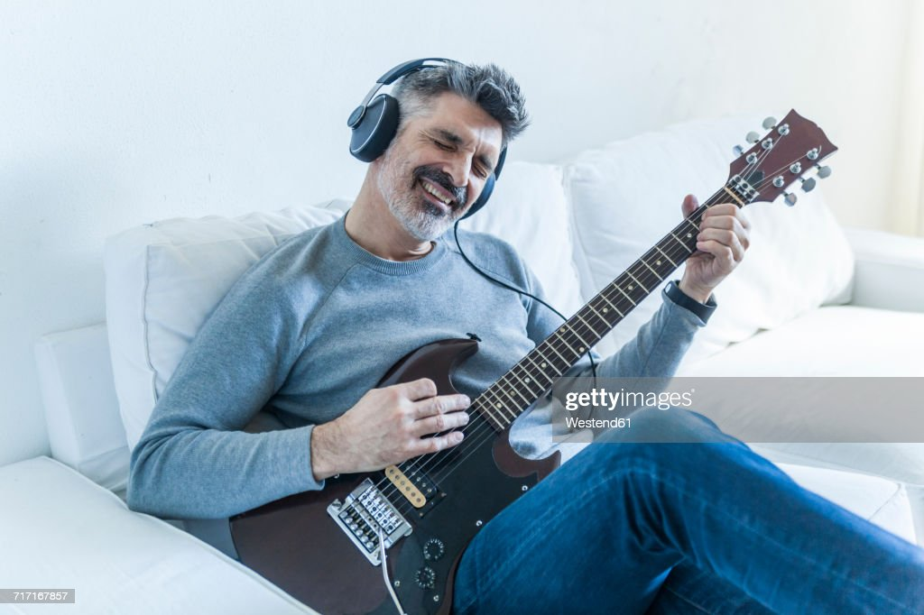 Mature man at home playing electric guitar and wearing headphones : Stock-Foto