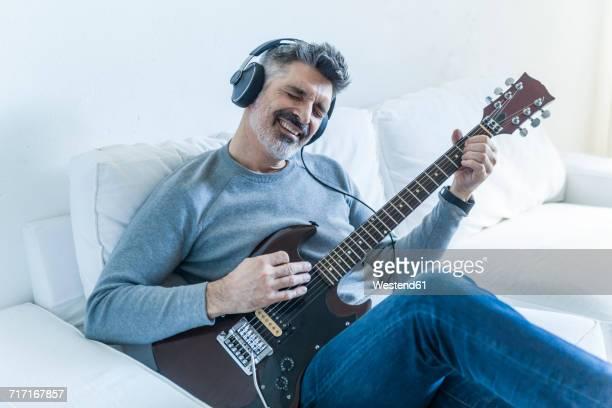 mature man at home playing electric guitar and wearing headphones - saiteninstrument spielen stock-fotos und bilder