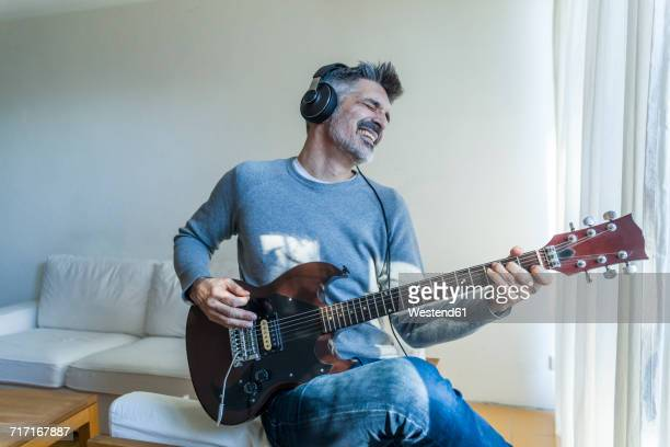 mature man at home playing electric guitar and wearing headphones - freizeit stock-fotos und bilder