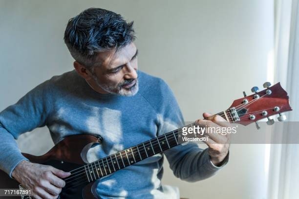 mature man at home playing electric guitar - gitarre stock-fotos und bilder