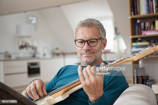 mature man at home playing guitar - freizeitaktivität stock-fotos und bilder