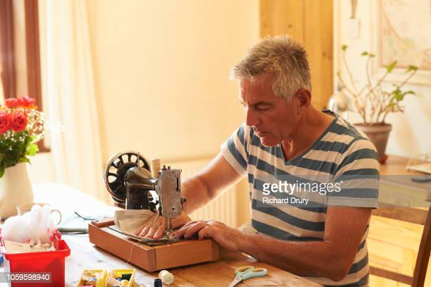 mature man at home sewing - sewing stock pictures, royalty-free photos & images
