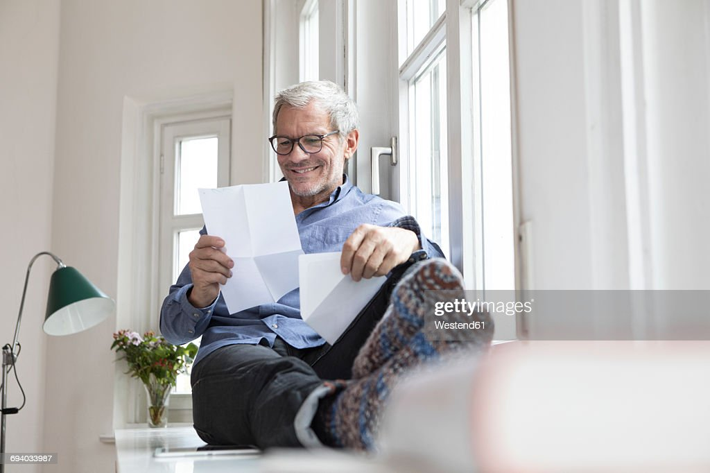 Mature man at home sitting at the window reading documents : Stock Photo